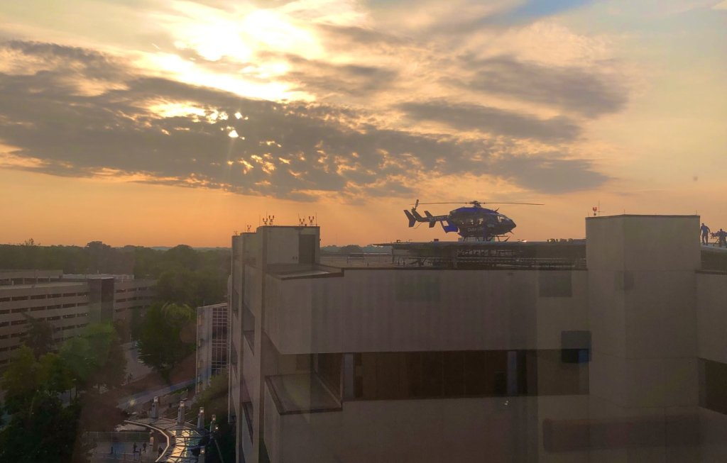 Hospital skyline with sunrise and helicopter.